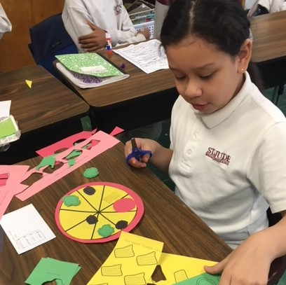 An elementary school girl works to cut out paper toppings for her fractions pizza