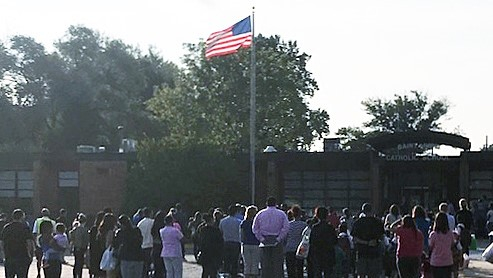The school community gathers in the main parking lot for the morning prayer and Pledge of Allegiance