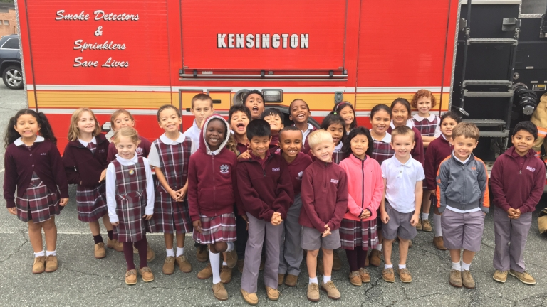 A group of pre-school students posing for a group photo in front of the fire truck that came on fire safety day