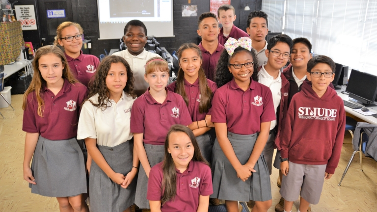 Former eighth grade students pose for a group shot in the computer lab, celebrating their production of the 2017-2018 yearbook