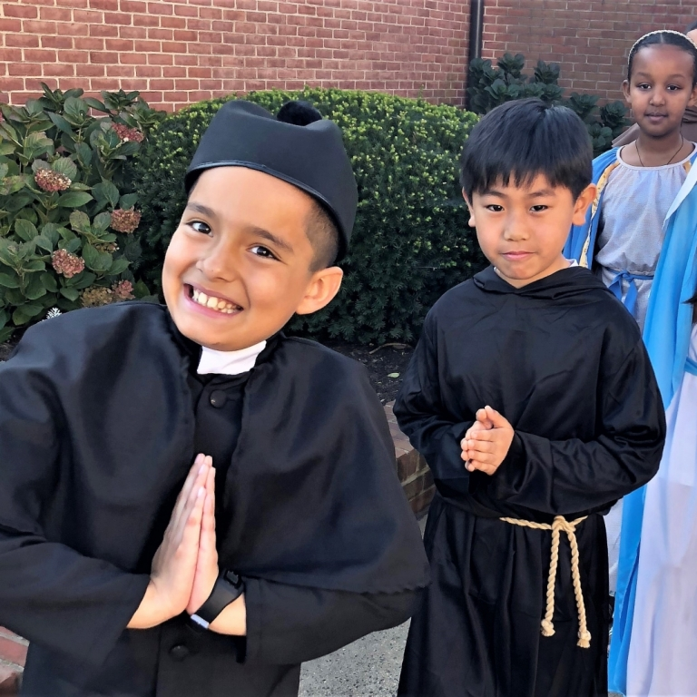 Fourth grade students pose as their saints for the wax museum