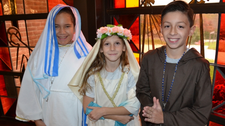Fourth grade saints in the Church posing as their wax museum saints, Saint Mother Theresa, Saint Therese of Lisieux, and Saint Francis of Assisi