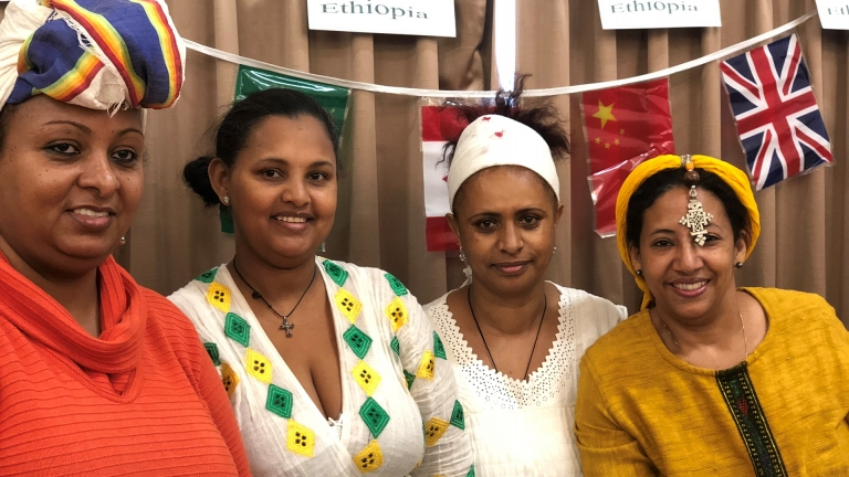 Four students' family members pose in their native dress before a spread of countries' flags for International Day 2018