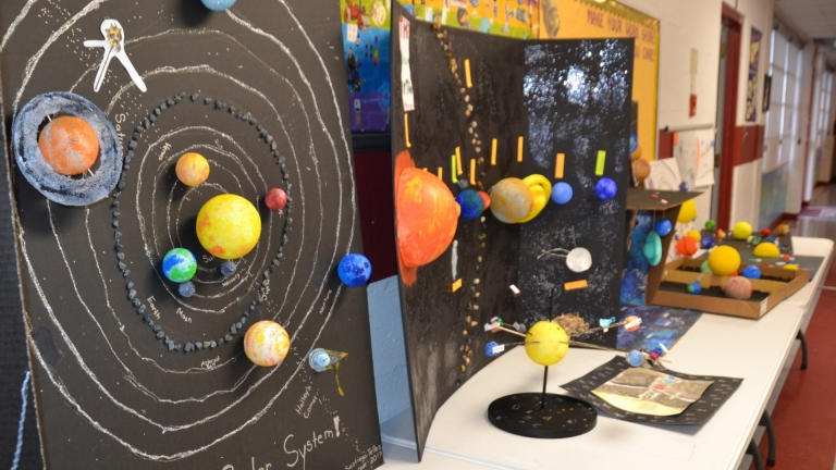 A collection of fifth grade solar system projects on display in the middle school hallway
