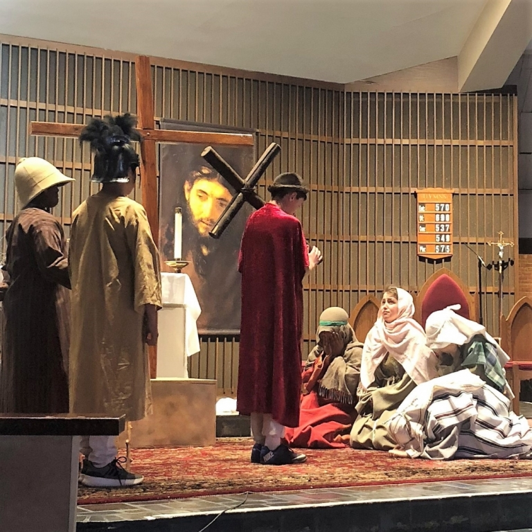Fifth grade students reenact the suffering and passion of Christ in the Living Stations