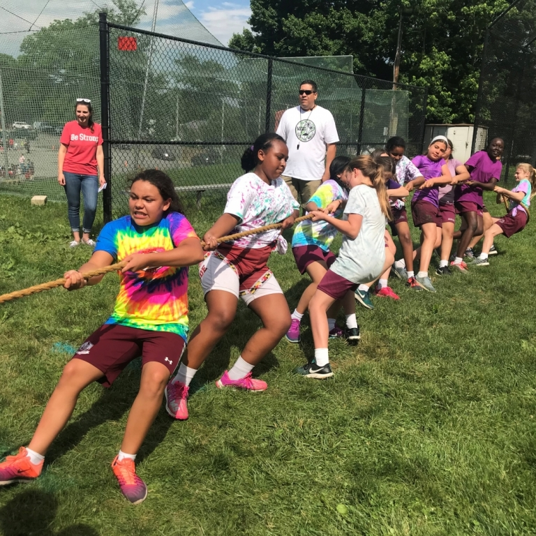 Seventh grade girls working hard to win a game of tug of war at field day 2018