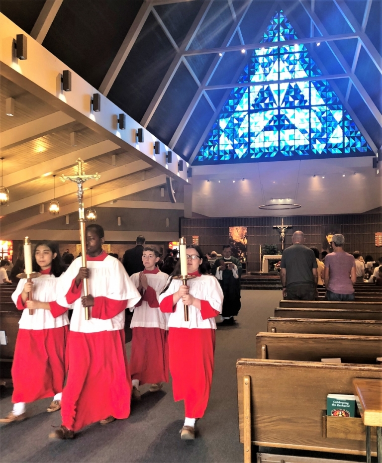 Altar servers lead the priest down the aisle during the recessional