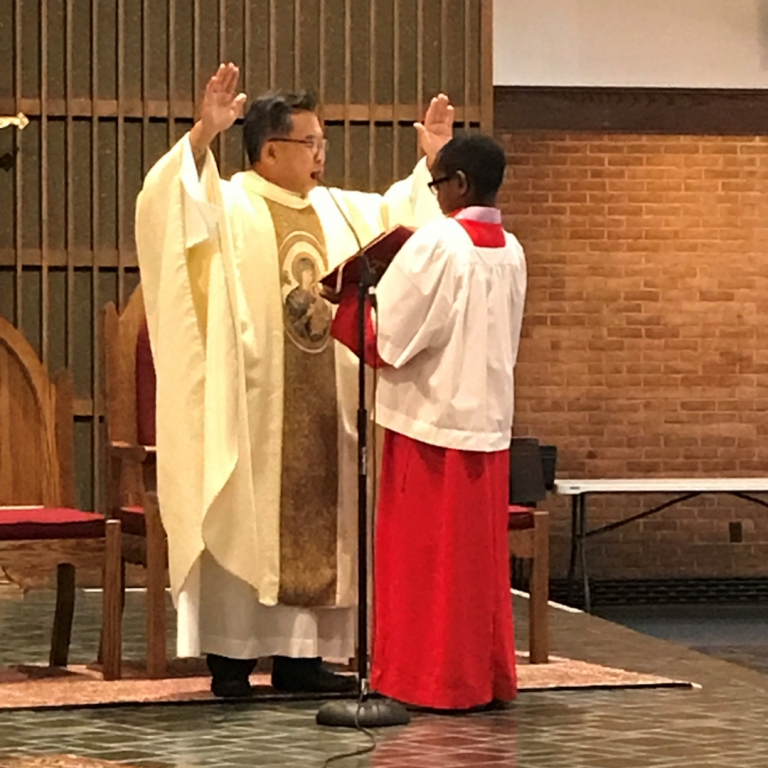 Pastor Father Lee saying mass and an eighth grade altar server