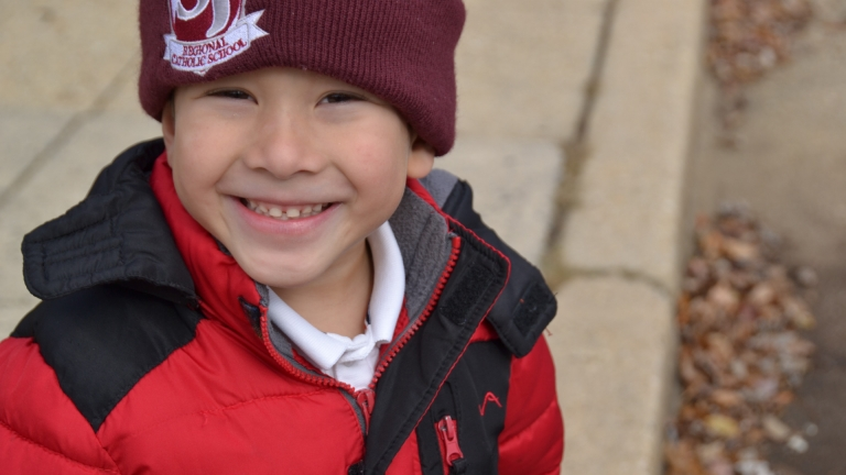 A preschool student smiling on the playground in his coat and hat