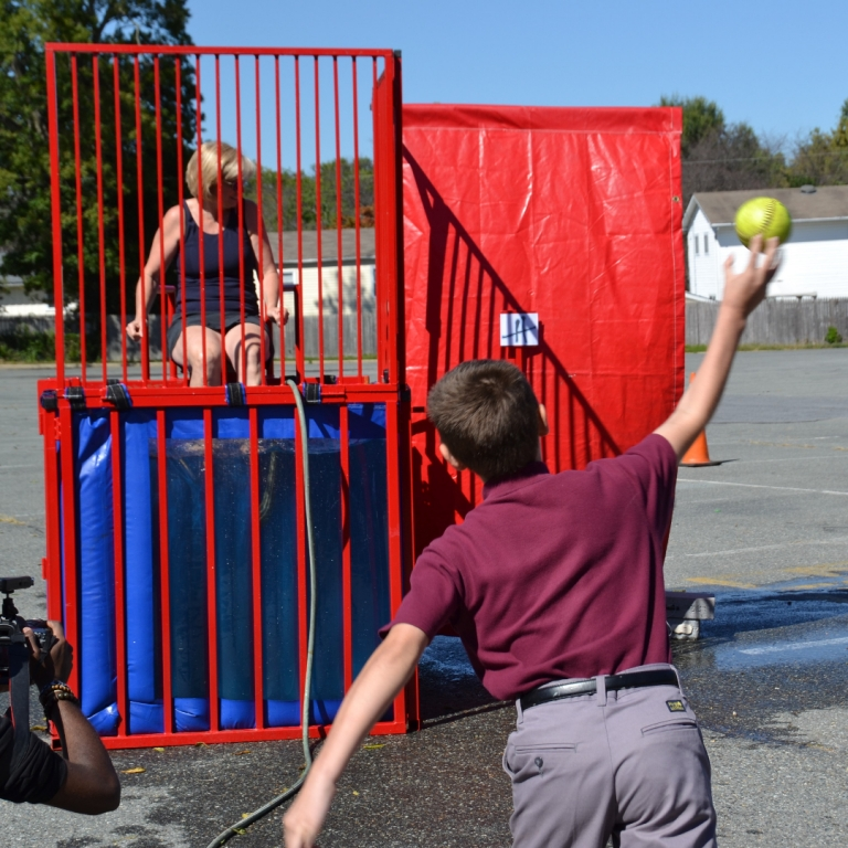 A sixth grade boy tries to dunk Vice Principal Mrs. Donatelli throwing out his first pitch