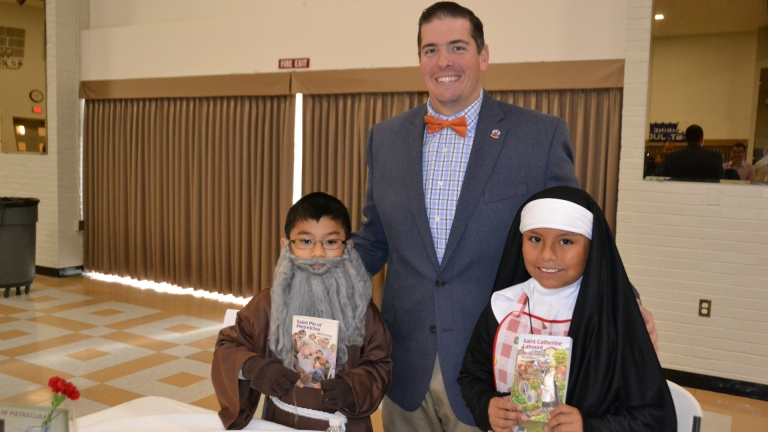 Principal Mr. Glenn Benjamin along with two fourth grade wax museum saints, Padre Pio and Saint Catherine Laboure